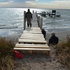 <div align=left>Jeremy (on the dock), Justin, and Gary inspect their work on the new dock extension. Yea! It was hard climbing over the sandy bluffs. No doubt the pelicans will love it. The dock is their favorite hangout when there are no people around. <em>Photo credit: Peggy Wilkinson</em></div>