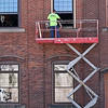Robert Graves an employee with Montachusett Contracting was replacing the windows on the building that houses Fitchburg Plumbing Supplu on Main Street on Tuesday as temperatures hit the high 80's. SENTINEL & ENTERPRISE/JOHN LOVE