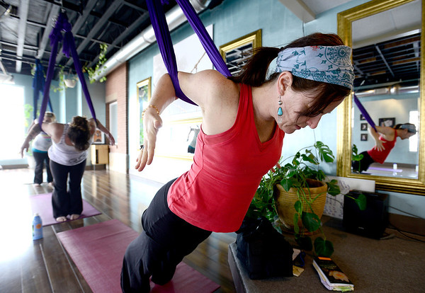 Katie Spear hangs from her silk during Aerial Yoga at Sangha Studios in Lafayette, Colorado February 28, 2013.  DAILY CAMERA/ MARK LEFFINGWELL