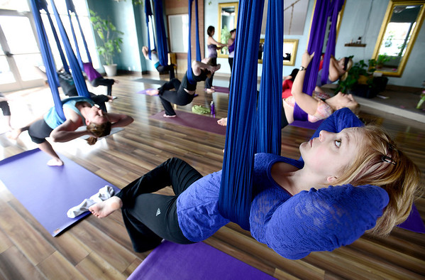 Sarah Leversee uses the silk for support during Aerial Yoga at Sangha Studios in Lafayette, Colorado February 28, 2013.  DAILY CAMERA/ MARK LEFFINGWELL