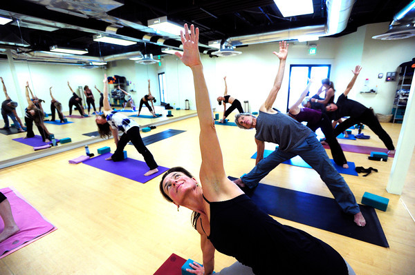 """Martha Triantafillides works in a triangle pose during the 50+! Strength & Grace Yoga at the little Yoga Studio in Boulder on Tuesday October 9, 2012. For more photos and a video of the class go to  <a href=""""http://www.dailycamera.com"""">http://www.dailycamera.com</a><br /> Photos by Paul Aiken / The Boulder Camera"""
