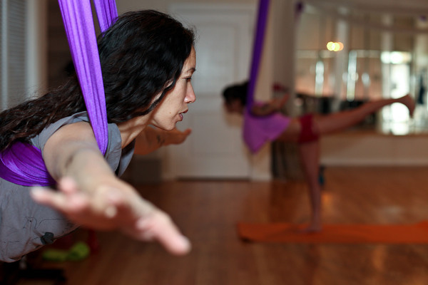 Sasha Viers, owner of Boulder Spirals, demonstrates a Forward Lean for her aerial yoga class on Saturday, May 19, 2012. (Morgan Varon/For the Camera)