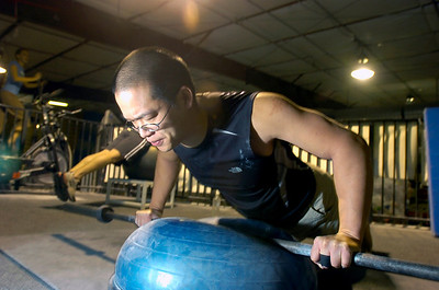 Ethan Tsai does pushups on a Bosu Ball during the Animal Strength workout at the Spot Gym in Boulder on Wednesday December 2, 2009. Watch a video of the workout and see more photos at www.dailycamera.com Photo by Paul Aiken / The Camera December 2, 2009.