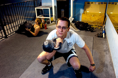 Mike Linck does squats with a kettle bell during the Animal Strength workout at the Spot Gym in Boulder on Wednesday December 2, 2009. Watch a video of the workout and see more photos at www.dailycamera.com Photo by Paul Aiken / The Camera December 2, 2009.
