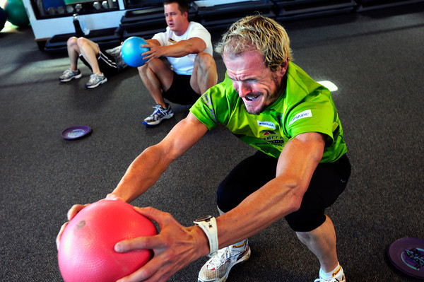 "Will Kelsay works hard in a squatting exercise during the Awesome Abs class at Rallysport in Boulder. Photo by Paul Aiken / The Boulder Camera / December 8, 2011<br /> For more photos and a video of the class go to  <a href=""http://www.dailycamera.com"">http://www.dailycamera.com</a>"