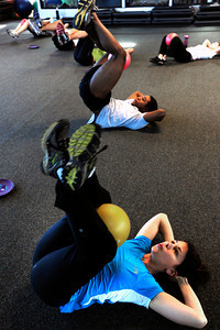 Lisa Zucker, bottom, and Gerett Burl work through a sit up exercise during the Awesome Abs class at Rallysport in Boulder. Photo by Paul Aiken / The Boulder Camera / December 8, 2011 For more photos and a video of the class go to www.dailycamera.com