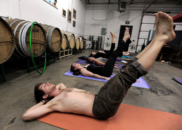 "Taran Volckhausen, of Boulder, at front, exercises with others during a beerasana yoga class at Asher Brewing Co. on Nautilus Court in Boulder. For more photos and video of the class go to  <a href=""http://www.dailycamera.com"">http://www.dailycamera.com</a><br /> Jeremy Papasso/ Camera"