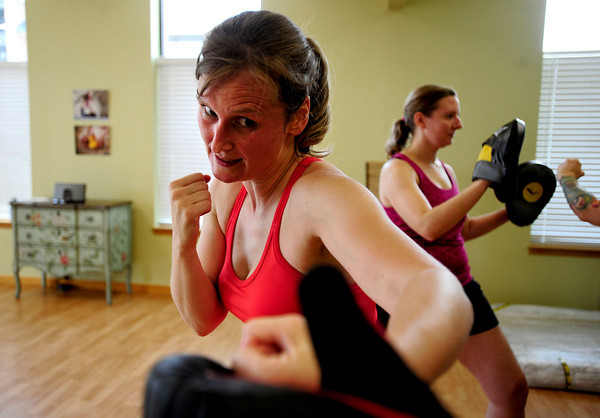 Instructor Lorene Nardell, of Longmont, punches a boxing glove at the Boxing workout for moms class in the Family Garden in Longmont, Colorado July 5, 2012. Rachel Woolf/ For the Daily Camera