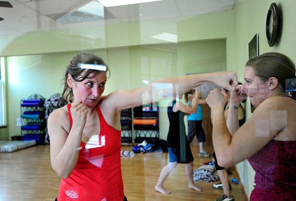 Instructor Lorene Nardell, of Longmont boxes against Alyson Boyce, of Fort Collins, at the Boxing workout for moms class in the Family Garden in Longmont, Colorado July 5, 2012. Rachel Woolf/ For the Daily Camera