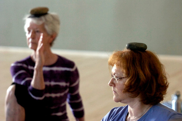 """From left to right Jo Ann Zender and Susannah Tenney use stones on their heads during a balance and stretching sequence during the Core Stone Yoga at the YMCA of Boulder Valley Arapahoe Branch on Thursday April 21, 2011.<br /> For more photos and a video of the class go to  <a href=""""http://www.dailycamera.com"""">http://www.dailycamera.com</a>.<br /> Photo by Paul Aiken / The Camera / <br /> Workout of the Week"""