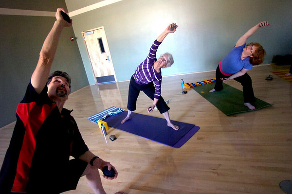 "Instructor Makann Burt leads Jo Ann Zender, and Susannah Tenney in an extended side angle pose during the Core Stone Yoga at the YMCA of Boulder Valley Arapahoe Branch on Thursday April 21, 2011.<br /> For more photos and a video of the class go to  <a href=""http://www.dailycamera.com"">http://www.dailycamera.com</a>.<br /> Photo by Paul Aiken / The Camera / <br /> Workout of the Week"