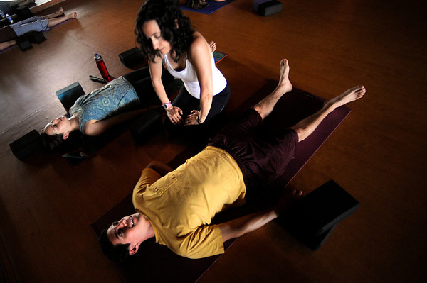 Instructor Laura Kupperman helps Alejandro Rodriguez work into a shoulder stretch during the Corerestore class at Corepower Yoga in Boulder on Thursday July 28, 2011. Genesa Falcao is pictured at left.<br /> For more photos and a video of the class <br /> Photo by Paul Aiken