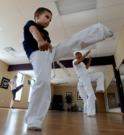"""Marcel Reyes, 7, appears to have good form on his kicks.<br /> Luis Carlos A. Silva, also known as Mestre Lucas Corvo ( Lucas the Crow), teaches Capoeira classes.<br /> For more photos and a video of Capoeira, go to  <a href=""""http://www.dailycamera.com"""">http://www.dailycamera.com</a><br /> Cliff Grassmick / June 16, 2011"""