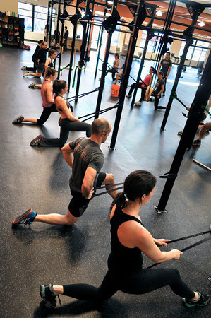 """Eric Roza, second from front, Faye Stech, left, and Kendra Lee stretch after working out at Crossfit Sanitas in Boulder on Monday Feb. 18, 2013. DAILY CAMERA/ JESSICA CUNEO. <br /> To watch a video and see more photos go to  <a href=""""http://www.dailycamera.com"""">http://www.dailycamera.com</a>."""