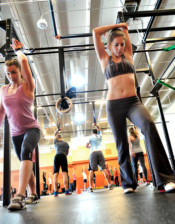 "Kendra Lee, left, and Faye Stech stretch at Crossfit Sanitas in Boulder on Monday Feb. 18, 2013. DAILY CAMERA/ JESSICA CUNEO. <br /> To watch a video and see more photos go to  <a href=""http://www.dailycamera.com"">http://www.dailycamera.com</a>."