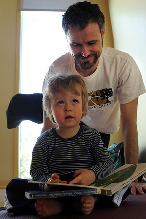 """Phoenix Hoelle reads as his dad, John, back,  does family yoga class.<br /> Katie Wise teaches Family Yoga at Yo Mama Yoga in Boulder.<br /> For more photos and a video of the class, go to  <a href=""""http://www.dailycamera.com"""">http://www.dailycamera.com</a>.<br /> Cliff Grassmick/ March 19, 2011"""