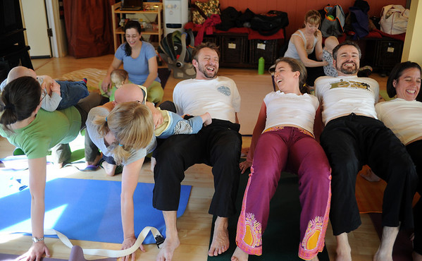 """Katie Wise, third from the right, gets the group to form a tunnel after completing the yoga train. Two moms can do this an nurse at the same time.<br /> Katie Wise teaches Family Yoga at Yo Mama Yoga in Boulder.<br /> For more photos and a video of the class, go to  <a href=""""http://www.dailycamera.com"""">http://www.dailycamera.com</a>.<br /> Cliff Grassmick/ March 19, 2011"""