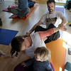 """Katie Wise talks to her son, Phoenix, while her husband, John, holds her arms.Zac and Cindy Zoet, back left, are doing the same pose.<br /> Katie Wise teaches Family Yoga at Yo Mama Yoga in Boulder.<br /> For more photos and a video of the class, go to  <a href=""""http://www.dailycamera.com"""">http://www.dailycamera.com</a>.<br /> Cliff Grassmick/ March 19, 2011"""