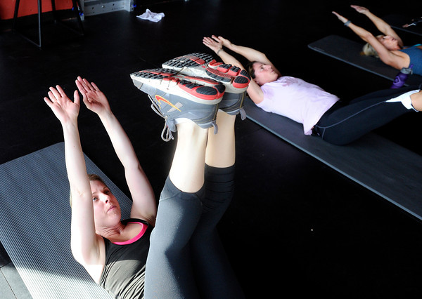 """Elizabeth Rao, left, Brooke Davison and Noelle Roshko work out their abs during a Fitwall workout class on Friday, Feb. 10, at the Fortis Fitness Training gym on Glenwood Drive in Boulder. For more photos and video of the class go to  <a href=""""http://www.dailycamera.com"""">http://www.dailycamera.com</a><br /> Jeremy Papasso/ Camera"""