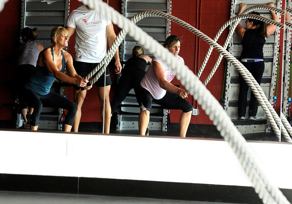 """Noelle Roshko, front left, and Brooke Davison, front right, work out with ropes while others work out on the wall during a Fitwall workout class on Friday, Feb. 10, at the Fortis Fitness Training gym on Glenwood Drive in Boulder. For more photos and video of the class go to  <a href=""""http://www.dailycamera.com"""">http://www.dailycamera.com</a><br /> Jeremy Papasso/ Camera"""