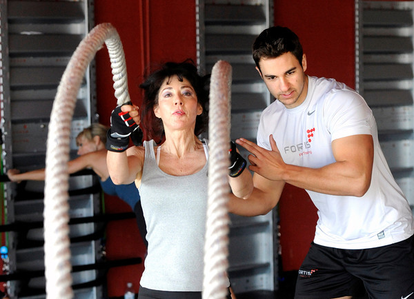 "Fortis Fitness owner and instructor Jeremiah Dargis helps Patti Stricklin with her form while working out with ropes during a Fitwall workout class on Friday, Feb. 10, at the Fortis Fitness Training gym on Glenwood Drive in Boulder. For more photos and video of the class go to  <a href=""http://www.dailycamera.com"">http://www.dailycamera.com</a><br /> Jeremy Papasso/ Camera"