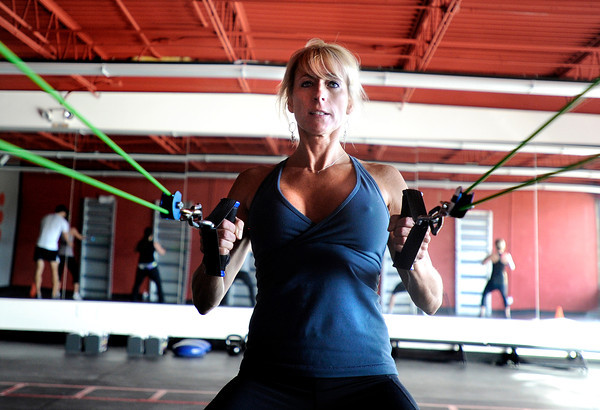 """Noelle Roshko, of Boulder, works her arms and back with bungees during a Fitwall workout class on Friday, Feb. 10, at the Fortis Fitness Training gym on Glenwood Drive in Boulder. For more photos and video of the class go to  <a href=""""http://www.dailycamera.com"""">http://www.dailycamera.com</a><br /> Jeremy Papasso/ Camera"""