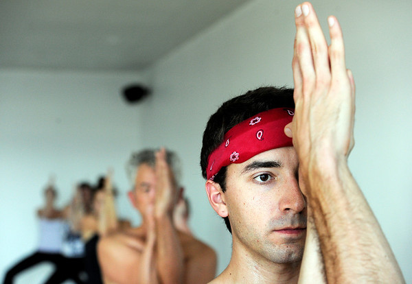 """Matt Lanterman, right, concentrates while exercising during a Forrest Yoga class on Friday, Dec. 9, at the Yoga Pod on 29th Street in Boulder. For more photos and video of the class go to  <a href=""""http://www.dailycamera.com"""">http://www.dailycamera.com</a><br /> Jeremy Papasso/ Camera"""