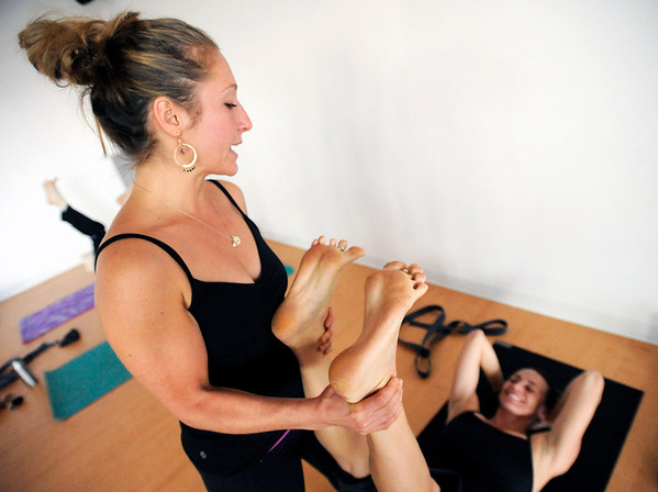 "Yoga Instructor Jo Schaalman, left, helps Kirsten Warner with her pose during a Forrest Yoga class on Friday, Dec. 9, at the Yoga Pod on 29th Street in Boulder. For more photos and video of the class go to  <a href=""http://www.dailycamera.com"">http://www.dailycamera.com</a><br /> Jeremy Papasso/ Camera"