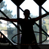 "Jennifer Jones, is silhouetted by a window while working out during a Hoop Dance Fitness class on Tuesday, Aug. 28, at the RallySport Health and Fitness Club in Boulder. For more photos of the workout go to  <a href=""http://www.dailycamera.com"">http://www.dailycamera.com</a><br /> Jeremy Papasso/ Camera"