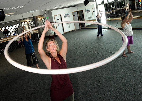 "Instructor Kristina Sutcliffe, front, demonstrates an over-the-head technique during a Hoop Dance Fitness class on Tuesday, Aug. 28, at the RallySport Health and Fitness Club in Boulder. For more photos of the workout go to  <a href=""http://www.dailycamera.com"">http://www.dailycamera.com</a><br /> Jeremy Papasso/ Camera"