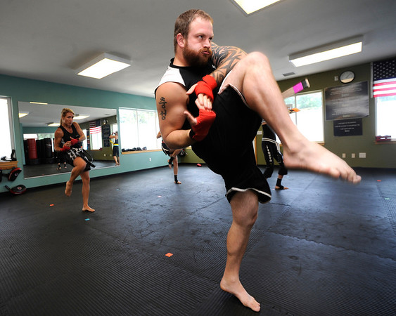 "Jamie Maples performs a knee strike during a kickboxing class at itsera Family Fitness in Niwot on Thursday August 11, 2011.<br /> For more photos and a video from the class go to  <a href=""http://www.dailycamera.com"">http://www.dailycamera.com</a><br /> Photo by Paul Aiken  August 11, 2011."
