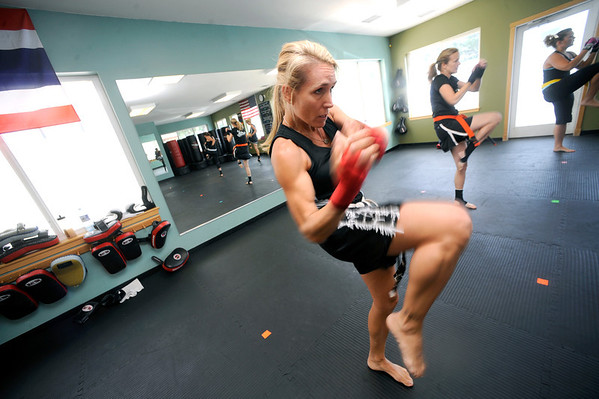 "Anne McCullick Owner and Instructor works on a knee strike  during a kickboxing class at itsera Family Fitness in Niwot on Thursday August 11, 2011.<br /> For more photos and a video from the class go to  <a href=""http://www.dailycamera.com"">http://www.dailycamera.com</a><br /> Photo by Paul Aiken  August 11, 2011."