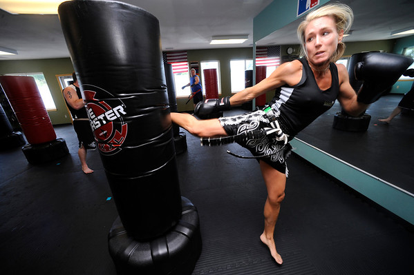 "Anne McCullick Owner and Instructor performs a kick against a bag  during a kickboxing class at itsera Family Fitness in Niwot on Thursday August 11, 2011.<br /> For more photos and a video from the class go to  <a href=""http://www.dailycamera.com"">http://www.dailycamera.com</a><br /> Photo by Paul Aiken  August 11, 2011."