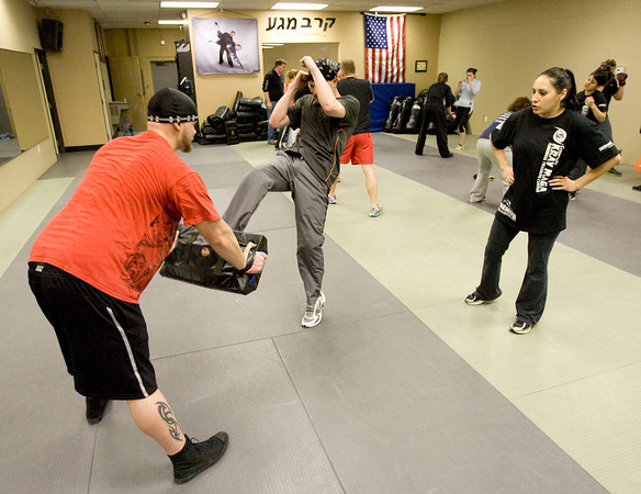 David Hilliard absorbs the kicks of Erick Schenkeir while instructor Jennifer Mancheg-Pena looks on at the Colorado Krav Maga Regional Training Center in Broomfield on Wednesday.