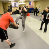 David Hilliard absorbs the kicks of Erick Schenkeir while instructor Jennifer Mancheg-Pena looks on at the Colorado Krav Maga Regional Training Center in Broomfield on Wednesday.