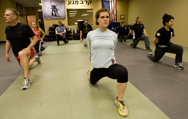 Maga1.jpg Mike Welsh, left Heather Underwood, center, and Andrea Herrera and stretch during warm-ups at the Colorado Krav Maga Regional Training Center in Broomfield on Wednesday.