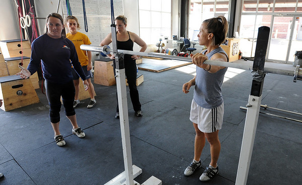 "Olympic Lifter Carissa Gump, left,  explains the best way to clean and jerk the bar.<br /> A class of Olympic weight lifting was taught at CrossFit in Boulder by David Miller and Randy Hauer.<br />  For more photos and a video of the workout, go to  <a href=""http://www.dailycamera.com"">http://www.dailycamera.com</a>.<br /> Cliff Grassmick / November 21, 2009"