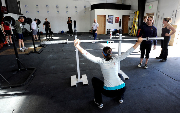 Amy Santamaria attempts the overhead lifting as  Olympian Carissa Gump, right, looks on.<br /> A class of Olympic weight lifting was taught at CrossFit in Boulder by David Miller and Randy Hauer.<br /> Cliff Grassmick / November 21, 2009