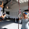 Julie Rappaport-Mitchell, left, pulls herself up while Amy Santamaria prepares to do the same during the warm up session.<br /> A class of Olympic weight lifting was taught at CrossFit in Boulder by David Miller and Randy Hauer.<br /> Cliff Grassmick / November 21, 2009