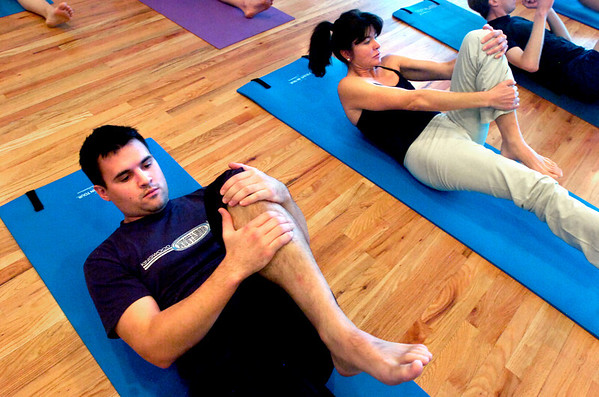 """Scott McLean at left, and Annette Means work on a core leg switching exercise during a pilates seminar for barefoot or minimal runners at the Pat Guyton Pilates in Boulder on Sunday January 10, 2010.  For more photos of the workout of the week go to  <a href=""""http://www.dailycamera.com"""">http://www.dailycamera.com</a>.<br /> Photo by Paul Aiken / The Boulder Camera / January 10, 2010"""