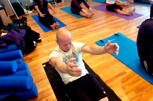 """Isaac Darnell does a core lift / sit up during a pilates seminar for barefoot or minimal runners at the Pat Guyton Pilates in Boulder on Sunday January 10, 2010.  For more photos of the workout of the week go to  <a href=""""http://www.dailycamera.com"""">http://www.dailycamera.com</a>.<br /> Photo by Paul Aiken / The Boulder Camera / January 10, 2010"""