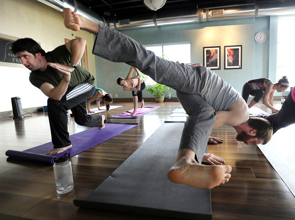 "Chris Swearingen, left, and Matt Clemente, both of Denver, hold their poses during a Reflective Frequency Yoga class on Thursday, Jan. 24, at Sangha Studios on Front Street in Louisville. For a video about the yoga class go to  <a href=""http://www.dailycamera.com"">http://www.dailycamera.com</a> <br /> Jeremy Papasso/ Camera"