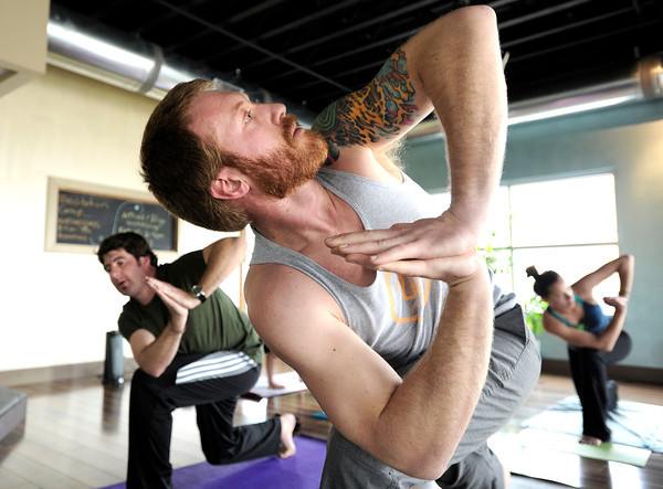 "Matt Clemente, center, and Chris Swearingen, both of Denver, hold their poses during a Reflective Frequency Yoga class on Thursday, Jan. 24, at Sangha Studios on Front Street in Louisville. For a video about the yoga class go to  <a href=""http://www.dailycamera.com"">http://www.dailycamera.com</a> <br /> Jeremy Papasso/ Camera"