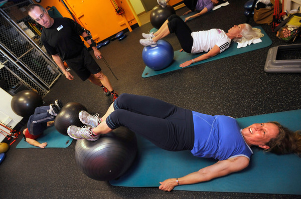 "Karie Kerner, bottom and Donna Jobert work on a core exercise with a ball as Glenn Marshman looks on in the Functional Fitness Small Group Training at One Boulder Fitness.  For more photos and a video of the class go to  <a href=""http://www.dailycamera.com"">http://www.dailycamera.com</a>.<br /> Photo by Paul Aiken / October 13, 2001..."