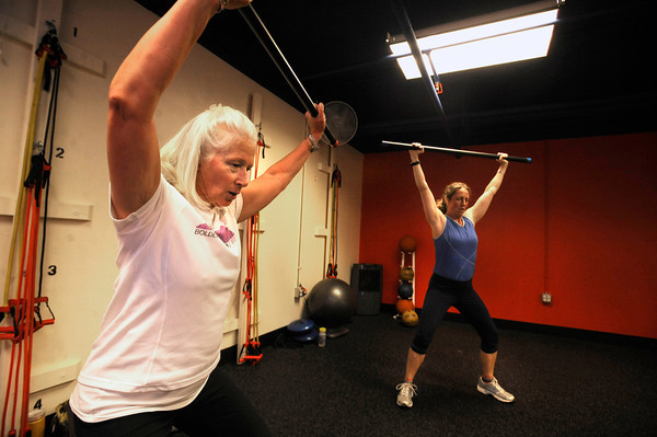 "Donna Jobert, left and Karie Kerner, work with a weighted bar exercise in the Functional Fitness Small Group Training at One Boulder Fitness.  For more photos and a video of the class go to  <a href=""http://www.dailycamera.com"">http://www.dailycamera.com</a>.<br /> Photo by Paul Aiken / October 13, 2001..."