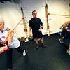 "Donna Jobert, left and Karie Kerner, work a one armed punching exercise with resistance bands as Glenn Marshman looks on in the Functional Fitness Small Group Training at One Boulder Fitness.  For more photos and a video of the class go to  <a href=""http://www.dailycamera.com"">http://www.dailycamera.com</a>.<br /> Photo by Paul Aiken / October 13, 2001..."