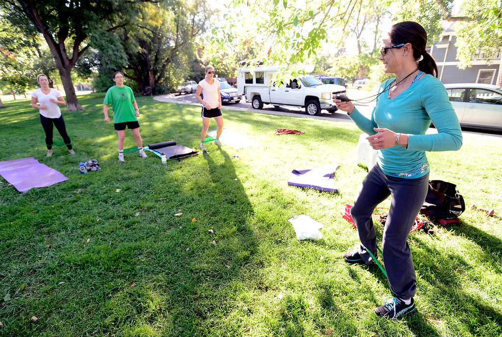 . From left to right Avery Oatman, Kate Kelsch and Lisa Shoemaker use resistance bands during a leg exercise as instructor Annette Bray sets the time for the drill in her ski conditioning class in North Boulder Park on Wednesday, Oct 2, 2013. For more photos and a video of the class go to www.dailycamera.com Paul Aiken / Camera
