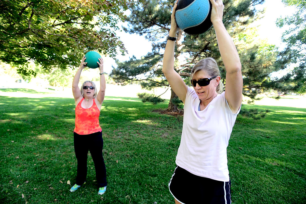 . Pat Lehman, left and Lisa Shoemaker work with exercise balls during instructor Annette Bray\'s ski conditioning class in North Boulder Park on Wednesday, Oct 2, 2013. For more photos and a video of the class go to www.dailycamera.com Paul Aiken / Camera