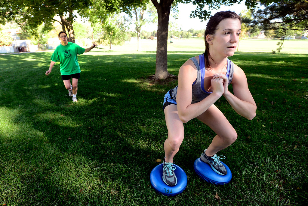 . Brooke Null does squats while Kate Kelsch does one a one leg stance during instructor Annette Bray\'s ski conditioning class in North Boulder Park on Wednesday, Oct 2, 2013. For more photos and a video of the class go to www.dailycamera.com Paul Aiken / Camera