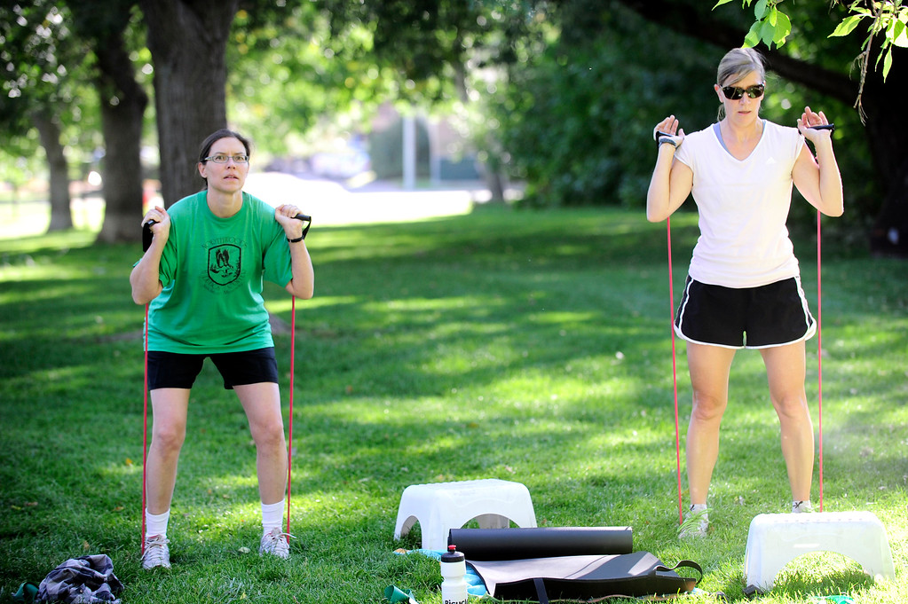. Kate Kelsch, left and Lisa Shoemaker use resistance bands during a squat leg exercise during instructor Annette Bray\'s ski conditioning class in North Boulder Park on Wednesday, Oct 2, 2013. For more photos and a video of the class go to www.dailycamera.com Paul Aiken / Camera
